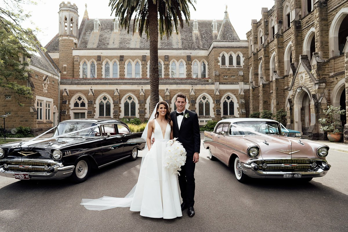 Bride And Groom Standing In Front Of Their Wedding Cars