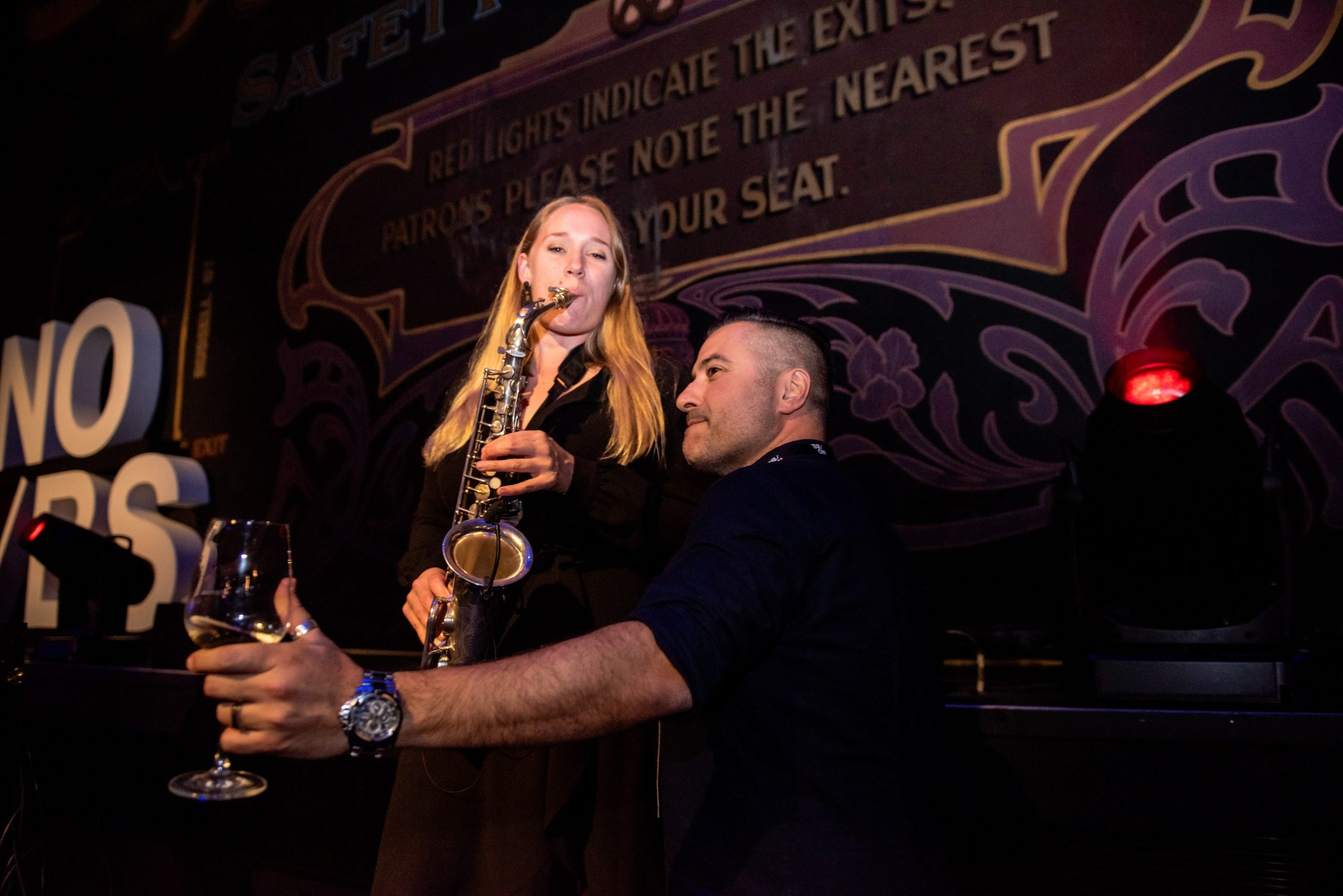 Female Sax Player With Guest With Wine In His Hand At Melbourne Conference Event