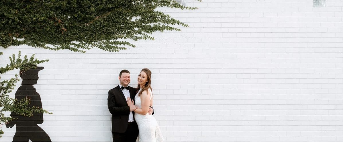 Bride And Groom Pose In Front Of Little Henri Thornbury