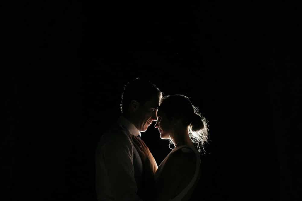Bride And Groom Pose In Front Of A Light on Dark Background At Coombe Yarra Valley