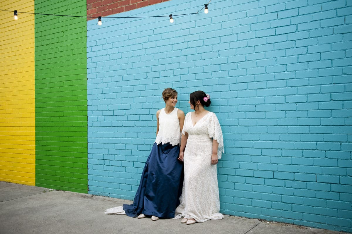 Two Brides Pose Against Colourful Wall In Melbourne Wedding Photographed by Natalie Davies